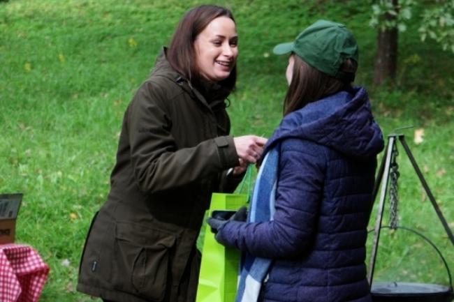 Gintarė Karelina iš VĮ valstybinės miškų urėdijos  įteikia dovanų Aukštadvario gimnazijos moksleiviams